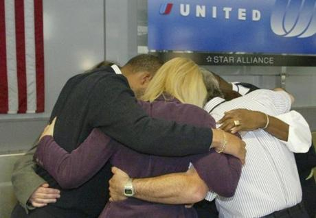 CROPPED VERSION OF ORIGINAL PHOTO -- United Airlines employees share a group embrace during a moment of silence at 8:46 a.m. Sept.11, 2003 at Boston's Logan Airport in memory of co-workers killed in the Sept.11, 2001 terrorist attacks. United and American Airlines flights originating from Boston were used in the attacks. (AP Photo/ Bizuayehu Tesfaye) Library Tag 09122003 Page One FOR BOSTONGLOBE.COM GALLERY ONLY!!!!!! airlinegallery